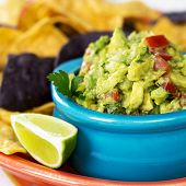 A bowl of fresh guacamole with corn tortilla chips and a wedge of lime. Intentional shallow depth of