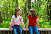 children sister friends talking relaxed sitting on the jungle park forest outdoor