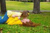 Daughter and mother nose kissing lying on park lawn outdoor