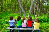 Children sister and friend girls sitting on park bench looking at forest and smiling