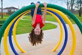 children kid girl upside down on a park playground ring game