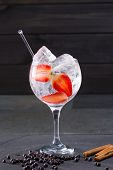 Gin tonic cocktail with strawberries ice cinnamon and juniper berries on black