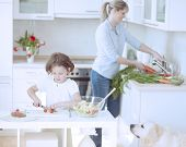 Mother and Daughter (8-9) preparing healthy meal in kitchen