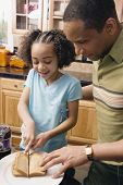 Father and daughter making peanut butter and jelly sandwich