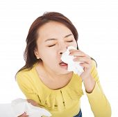 Young Woman With A An Allergy Sneezing Into Tissues