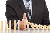 stock photo of risk  - businessman hand stop dominoes continuous toppled on the desk - JPG