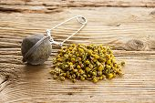 Dry Camomile With Tea Strainer On Old Wooden Table