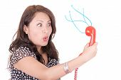 hispanic Woman looking into old telephone, communications concept