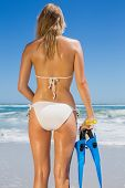 Fit woman in white bikini holding snorkeling gear on the beach on a sunny day