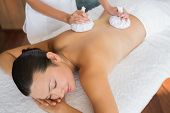 Content brunette getting a herbal compress massage at the health spa