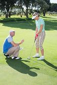 Man coaching his partner on the putting green on a sunny day at the golf course
