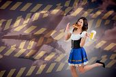 Pretty oktoberfest girl holding beer tankard and pretzel against cloudy sky