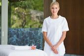 Smiling beauty therapist standing beside massage towel at the spa