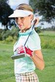 Female golfer standing holding her club smiling at camera on a sunny day at the golf course