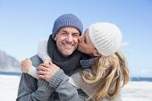 Attractive couple hugging on the beach in warm clothing on a bright but cool day