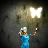 Young pretty woman in blue hat and dress holding balloon