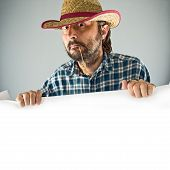 stock photo of wrangler  - Farmer with cowboy straw hat holding blank poster as copy space - JPG