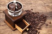 image of coffee grounds  - Vintage coffee bean grinder and fresh ground coffee on wooden top next coffee beans - JPG