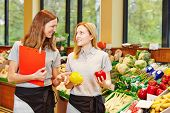 Store manager in supermarket teaching trainee in the vegetables section