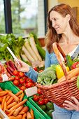 Attractive elderly woman buying vegetables with shopping list in a supermarket