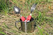 tourist spoon, fork and cup on grass background