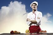 Young cheerful cook and ingredients flying in air