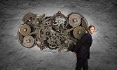 Young businessman carrying cogwheel mechanism on back