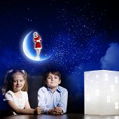 Cute little boy and girl looking at model of house