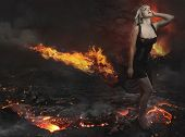 Beautiful blonde in a desolate landscape with a volcano of lava and fire river