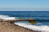 Coast Madeira With Jetty And Small Fishing Ship At Sea