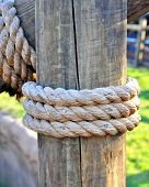 Three layers of rope tied around a wooden log