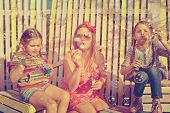 Beautiful mother and little daughters blowing soap bubbles together in summer