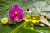 Set of pink orchid and stones ,massage oil,candle,on wet banana leaf