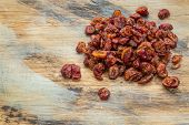 a pile of dried cranberries on a grunge painted wood background