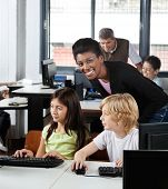Portrait of young female teacher with students at desk in computer lab