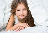Long-haired girl looks out from under the blanket