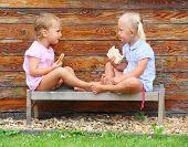 Children eating on the rural bench.