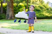 Cute Toddler Girl In Yellow Rubber Boots