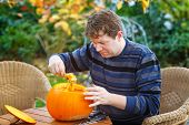 Young Man Making Halloween Pumpkin