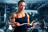 Young woman bodybuilder with barbell.