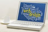 web design and development word cloud with binary background on laptop with a cup of coffee
