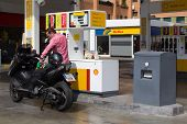 VALENCIA, SPAIN - JUNE 10, 2014: A man filling up his scooter at a Shell gas station in Valencia. Ac