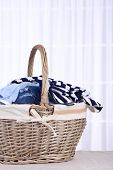 Colorful clothes in basket on table, on light background