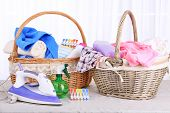 Colorful towels and clothes in baskets on table, on light background