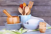 Composition of wooden cutlery, pan, bowl and cutting board on wooden background