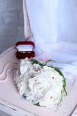 Beautiful wedding bouquet on   wooden chair on light background