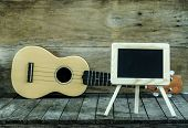 Ukulele guitar and blank blackboard on wooden background