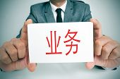 businessman sitting in a desk holding a signboard with the word business written in chinese in it