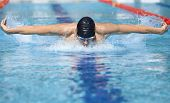 professional swimmer in cap breathing performing the butterfly stroke in swimming pool