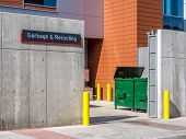 image of loading dock  - Garbage and recycling sign at a loading dock on a modern commercial building - JPG